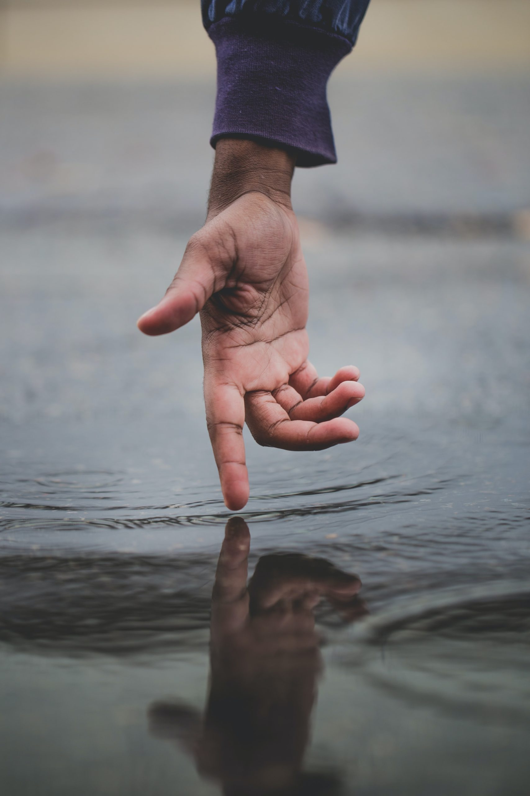 person touching body of water and creating ripples